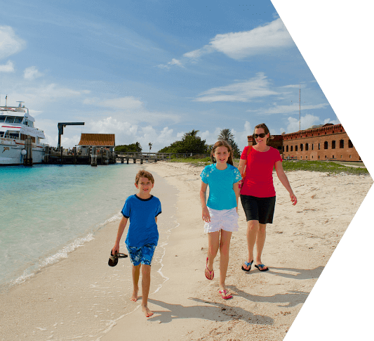 A mom and her young daughter and son walking along the shoreline in the Dry Tortugas National Park