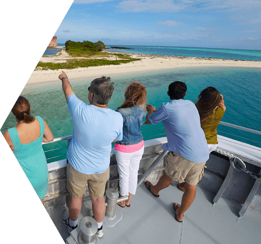 A middle-aged man flanked by two other women facing out towards the Dry Tortugas National Park from the deck of the Yankee Freedom III