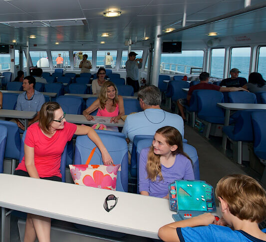 Mom smiling at her daughter while both seated at a table while onboard the Yankee Freedom on route to the Dry Tortugas